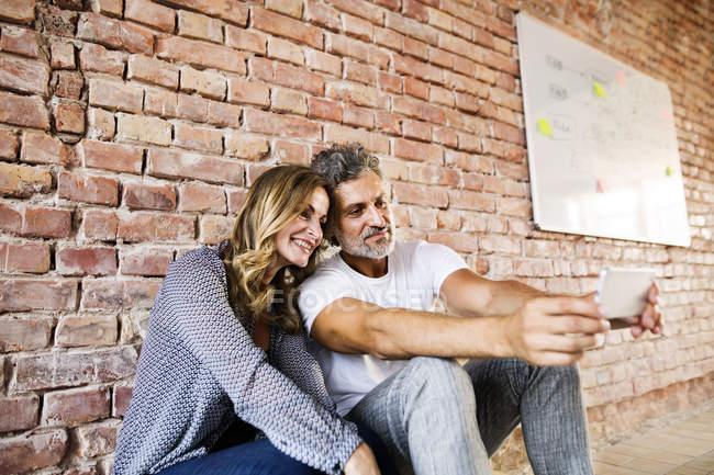 Бизнесмен и женщина сидят в новом офисе, делясь селфи — стоковое фото
