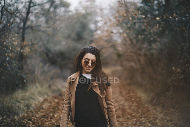 Portrait of smiling young woman in autumnal nature — Stock Photo