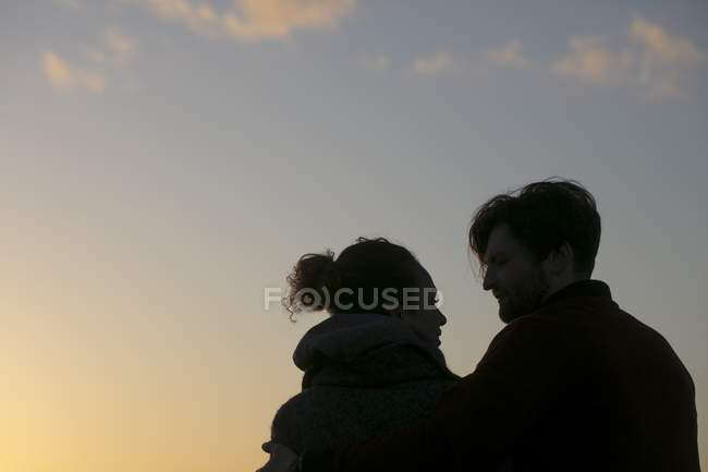 Silhouette of young couple outdoors at sunset — Stock Photo