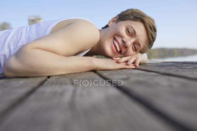 Portrait of laughing woman lying on jetty — стокове фото