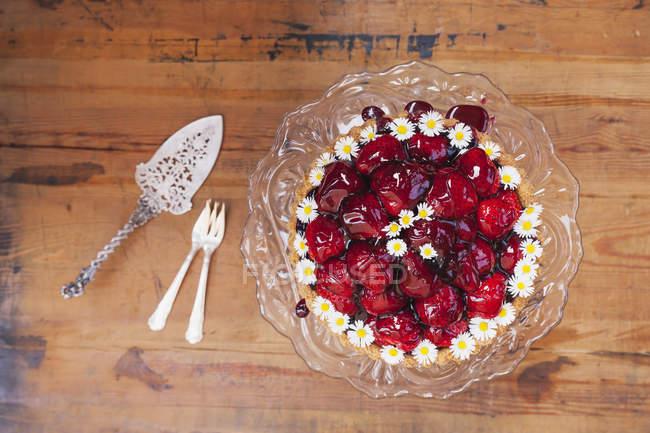 Домашній полуничний пиріг з червоним соком винограду глазур'ю і ромашки квітка прикраса на старому стенді торт — стокове фото