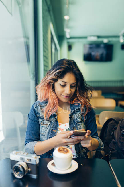 Smiling woman sitting in coffee shop looking at cell phone — Stock Photo