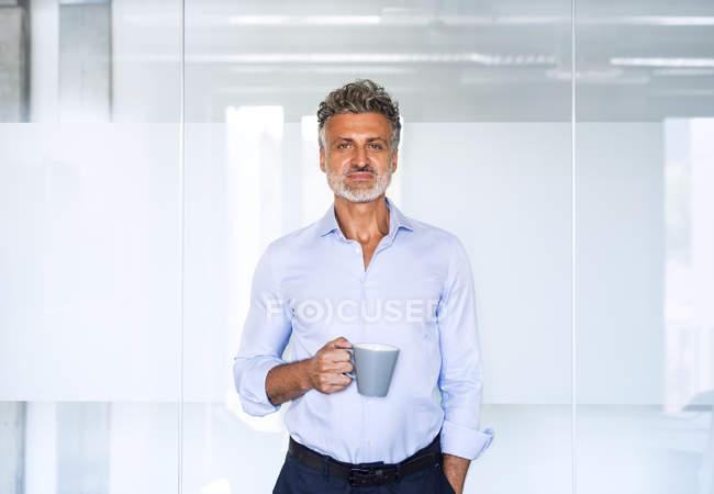 Портрет уверенного в себе взрослого бизнесмена, держащего кофейную кружку в офисе — стоковое фото