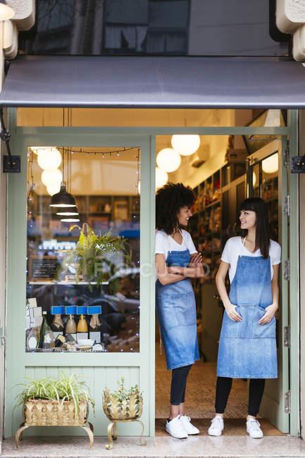 Deux femmes souriantes debout dans la porte d'entrée d'un magasin — Photo de stock