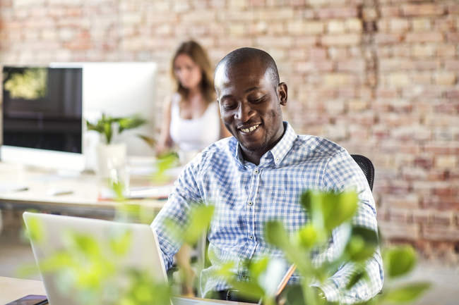 Smiling businessman using laptop at desk in office with colleague in background — Stock Photo