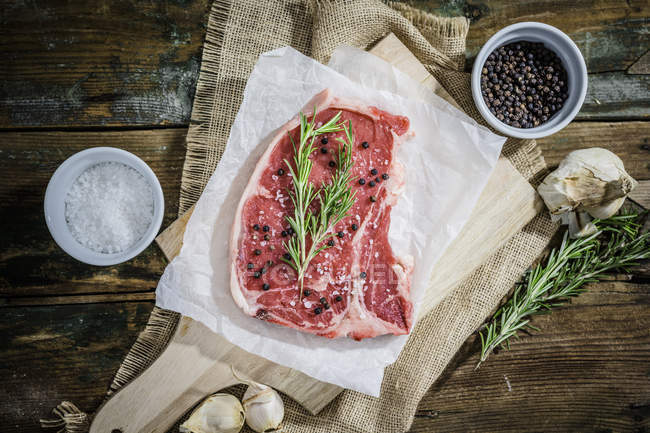 Raw beefsteak with rosemary, salt and pepper — Stock Photo