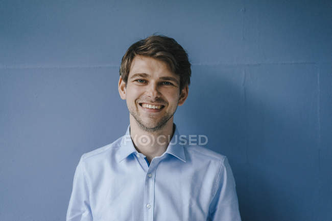 Portrait of smiling man in front of blue wall — Stock Photo