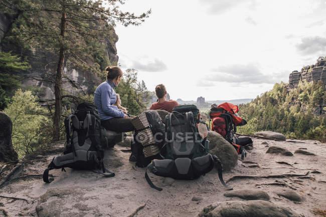 Alemania, Sajonia, Elba Montañas de piedra arenisca, amigos en un viaje de senderismo teniendo un descanso - foto de stock