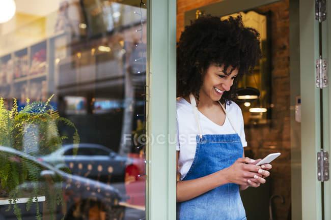 Улыбающаяся женщина с помощью мобильного телефона в входной двери магазина — стоковое фото