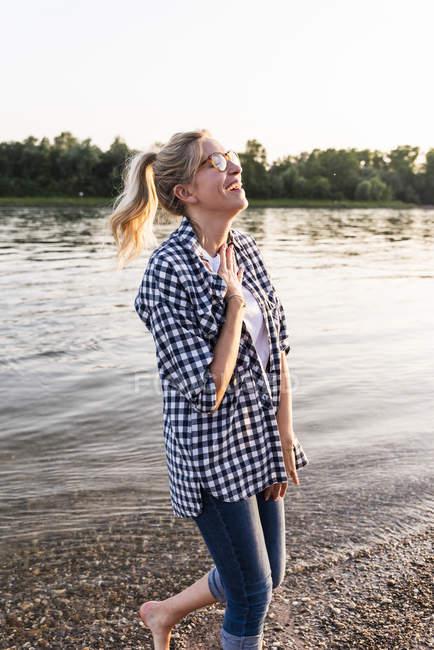 Ridere giovane donna a piedi sul fiume la sera — Foto stock