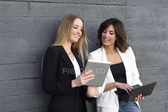 Duas mulheres de negócios com tablet e laptop — Fotografia de Stock