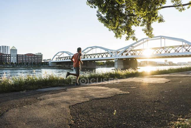 Jeune homme dribble basket à la rivière — Photo de stock