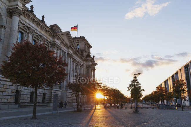 Germany, Berlin, Regierungsviertel, Reichstag building with German flags and Paul-Loebe-Building at sunset — Stockfoto