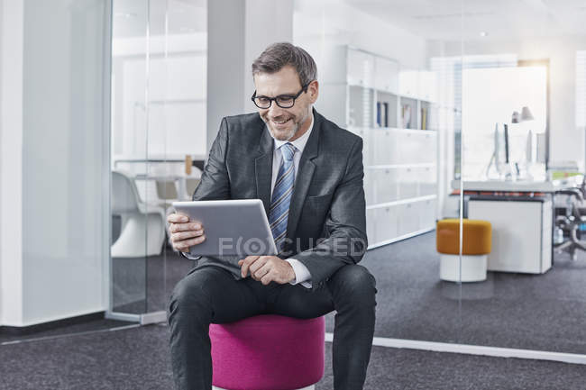 Smiling businessman using tablet in office — Stock Photo