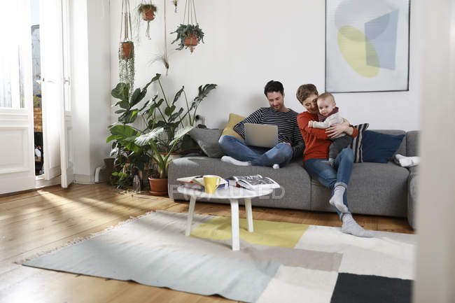 Family sitting on couch, using laptop — Stock Photo