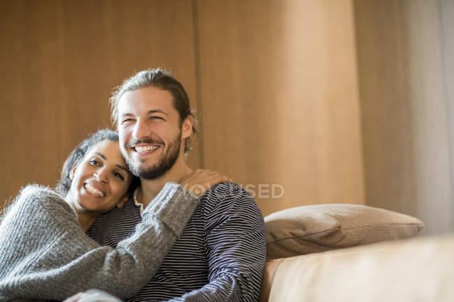 Ritratto di giovane coppia felice seduta sul divano — Foto stock