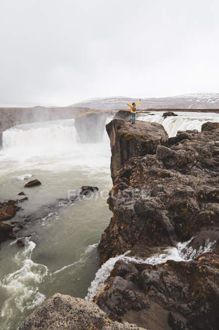 Islanda, donna in piedi alla cascata Godafoss con le braccia alzate — Foto stock