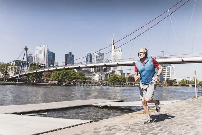 Homme mûr avec des écouteurs qui courent au bord de la rivière dans la ville — Photo de stock