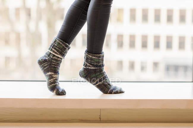 Женщина в трикотажных носках балансирует на подоконнике, частичный вид — стоковое фото