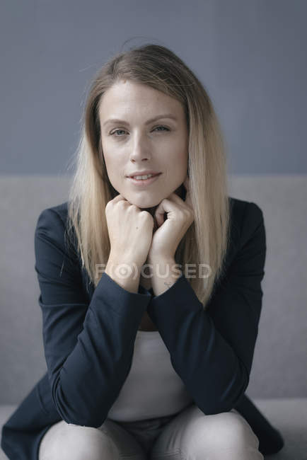 Portrait of businesswoman resting chin on hands and looking at camera — Stock Photo