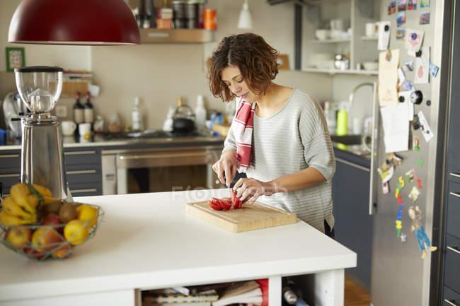 Mature woman cutting tomato in kitchen — Stock Photo