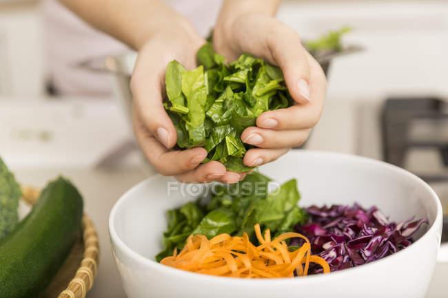 Manos poniendo lechuga fresca en un tazón con diferentes verduras - foto de stock