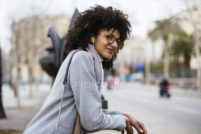 Улыбающаяся женщина с наушниками стоит в городе и смотрит в сторону — стоковое фото
