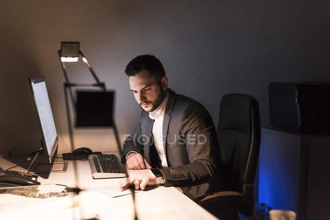 Homme d'affaires travaillant sur bureau dans le bureau la nuit — Photo de stock