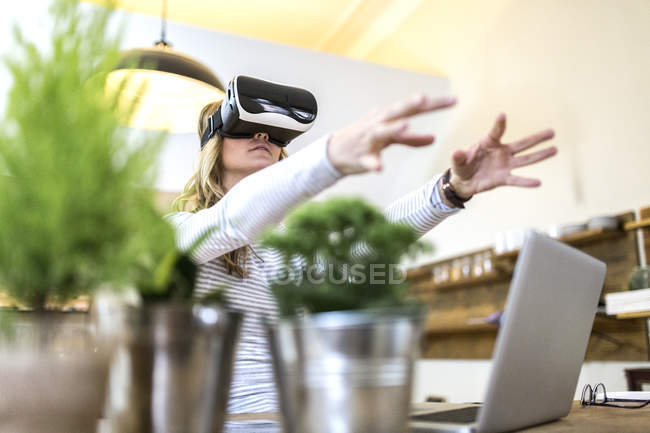 Woman with VR glasses and laptop at home — Stock Photo