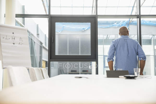 Rear view of african american businessman with flip chart in conference room — Stock Photo
