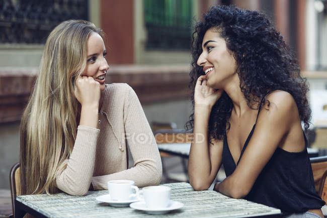 Two friends talking together in sidewalk cafe — Stock Photo