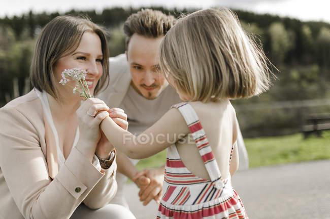 Niña dando flores madre mientras su padre está mirando - foto de stock