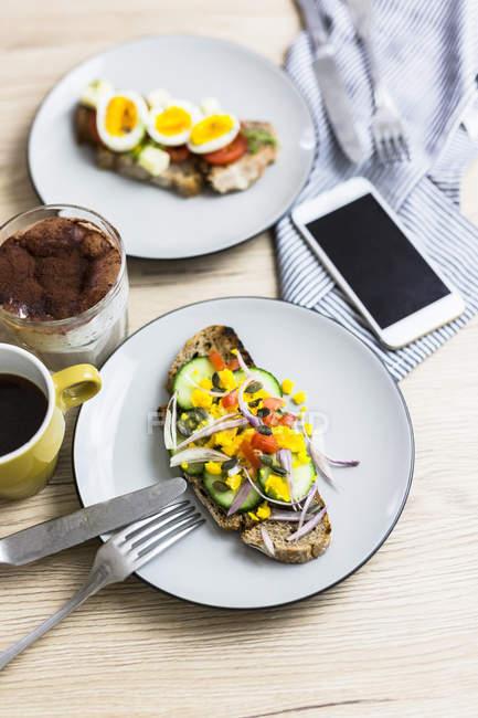 Вегетаріанський сніданок з хлібом, яйцями і шматочками огірків на тарілку, смартфон, латте Macchiato, кавова чашка — стокове фото