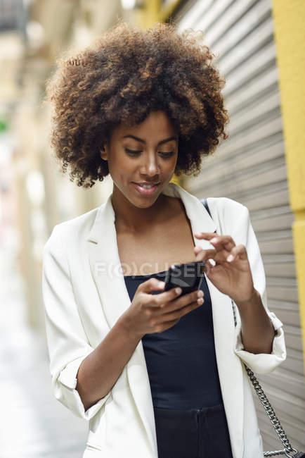 Ritratto di giovane donna sorridente con i capelli ricci che guarda il cellulare — Foto stock