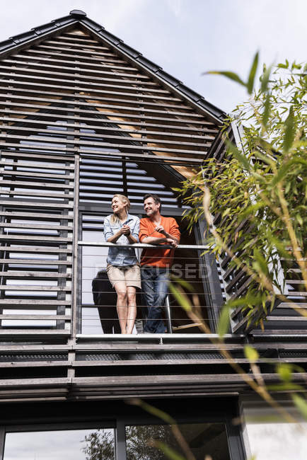 Smiling mature couple standing on balcony of their house — Stock Photo