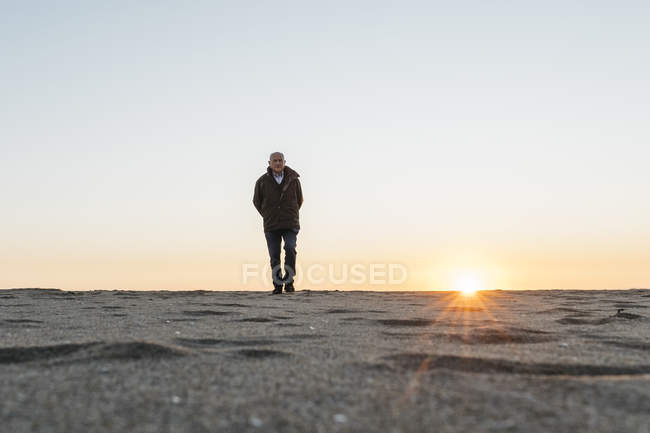 Lonely Senior man strolling at the beach, sunset sky on background — Stock Photo