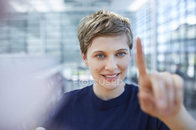 Portrait of blond businesswoman touching at glass pane — стокове фото