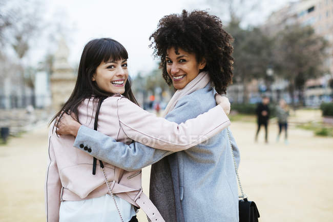Spain, Barcelona, portrait of two embracing smiling women in city turning around — стоковое фото