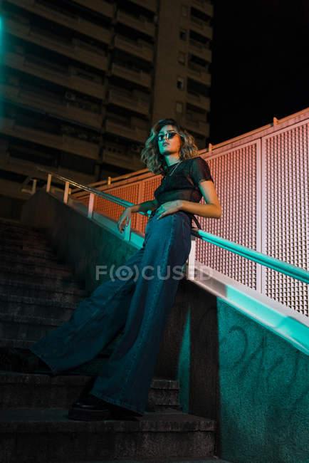 Стиль молодої жінки вночі в місті, в сонцезахисних окулярах. — стокове фото