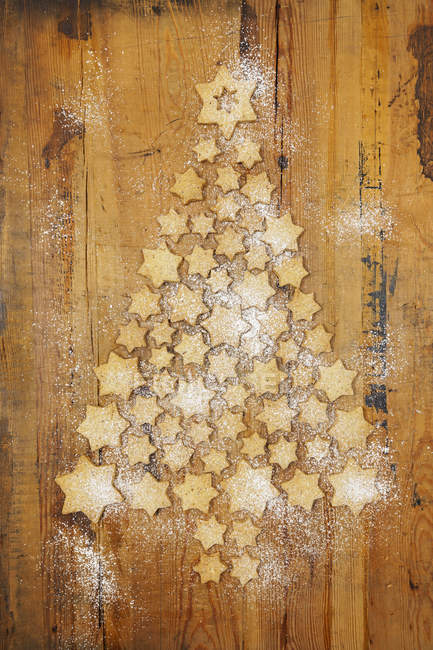 Star-shaped biscuits forming Christmas Tree on wooden  background — Photo de stock