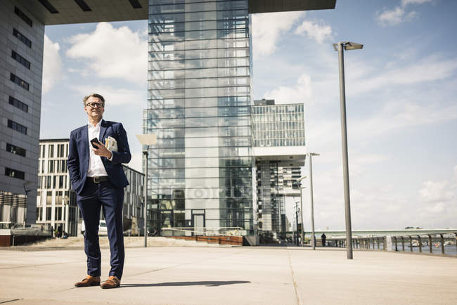 Mature businessman with cell phone standing outdoors — Stock Photo