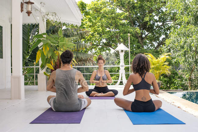 Two women and a man practicing yoga at the poolside — Stock Photo