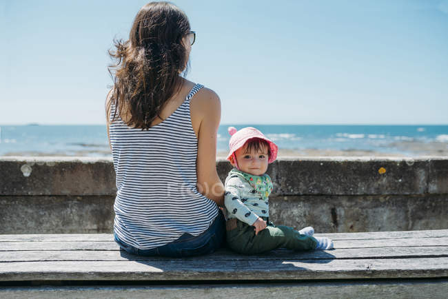 France, mother and baby girl sitting on a bench at beach promenade — Stock Photo
