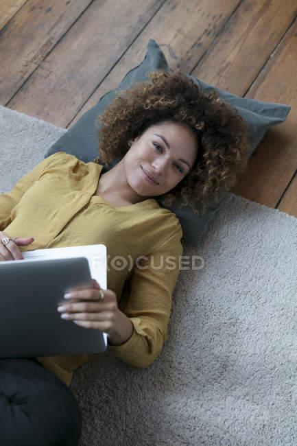 Усміхнена молода жінка, що лежить на підлозі вдома з ноутбуком — стокове фото
