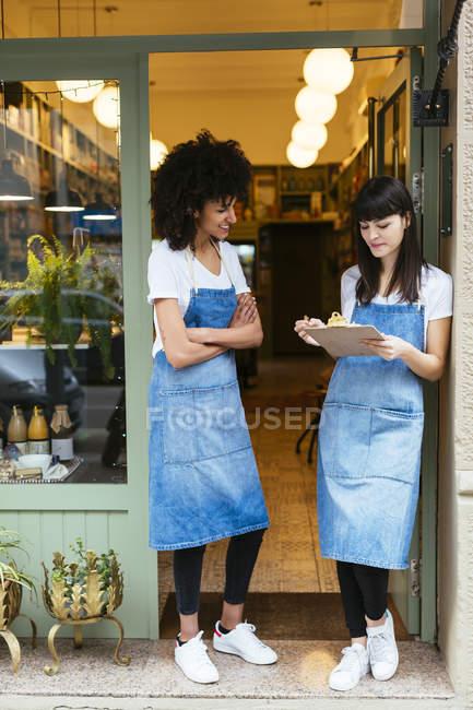 Deux femmes souriantes avec presse-papiers debout dans la porte d'entrée d'un magasin — Photo de stock