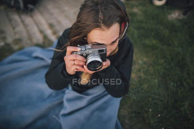 Молода жінка загорнута в ковдру і фотографує. — стокове фото