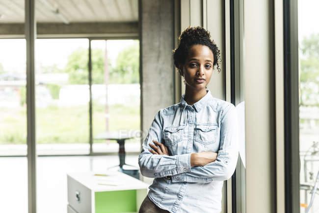 Jovem empresária confiante apoiando-se na janela no escritório moderno — Fotografia de Stock