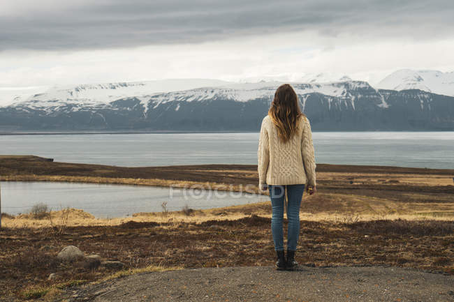 Iceland, woman standing at lakeside — Stock Photo