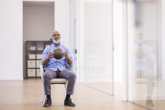 Африканский американский бизнесмен с кожаным мячом сидит на кресле в офисе — стоковое фото