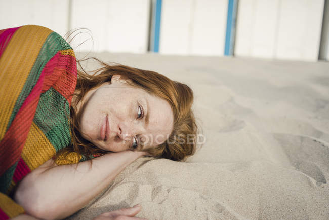Redheaded woman resting in sand on the beach — Stock Photo